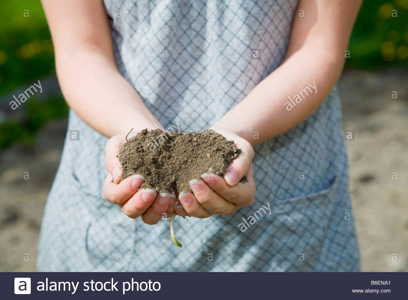 Mädchen mit Schmutz in ihren Händen Stockbild