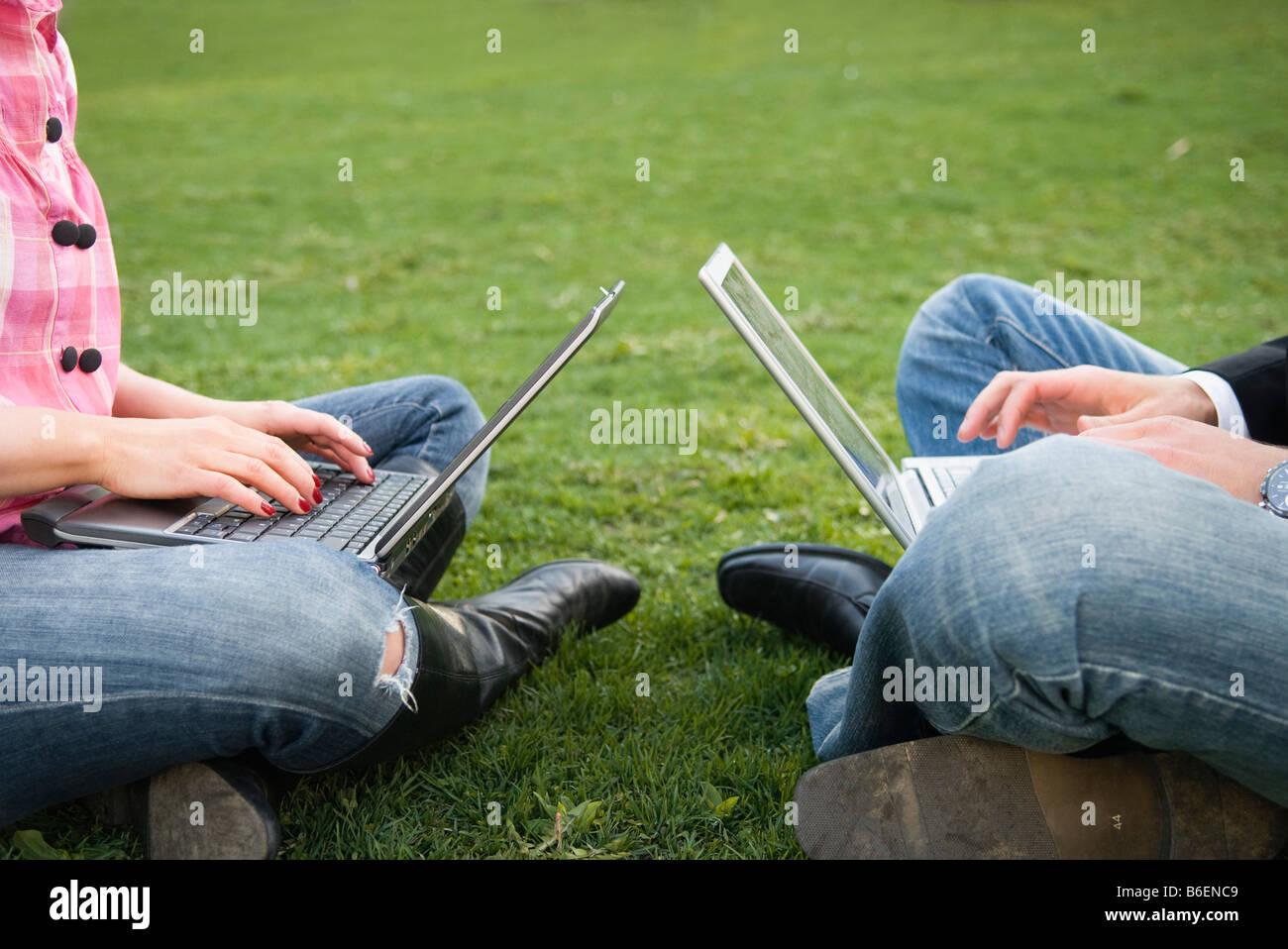 Mann und ein Mädchen einander gegenüber mit Computern Stockbild
