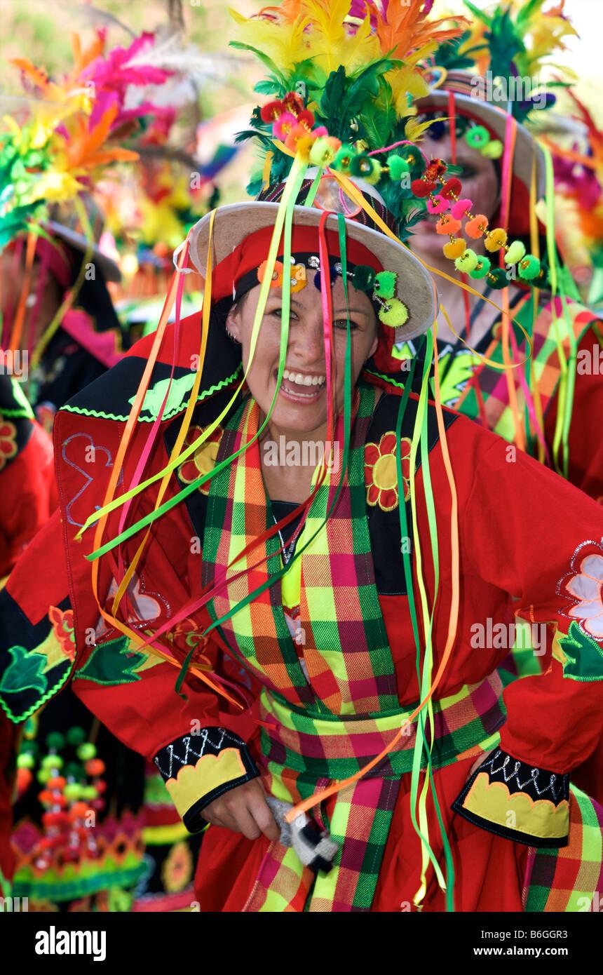 Lachende Mädchen im roten Kostüm mit Hut und Bändern Stockbild