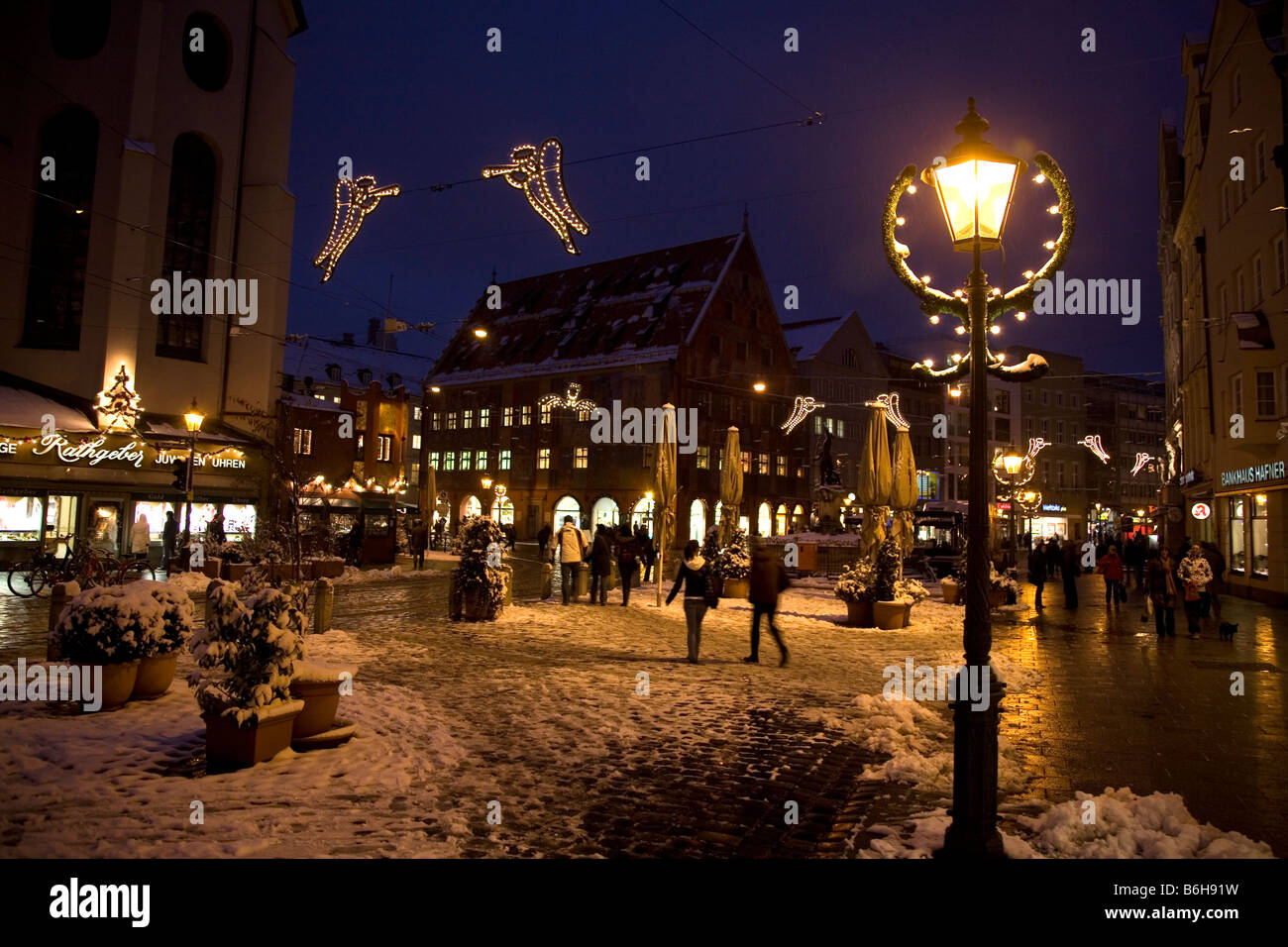 Die Menschen gehen auf einer verschneiten Abend-Straße in der charmanten Stadt Augsburg in Bayern, Deutschland. Stockbild