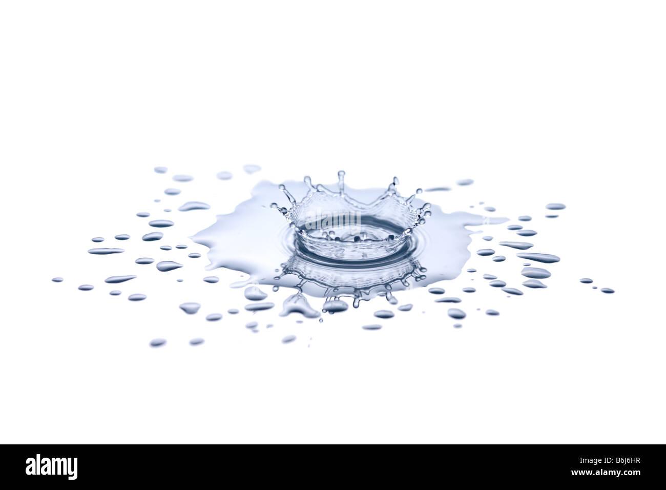 Einzelne Tropfen Spritzwasser in kleine Wasserpfütze Stockbild