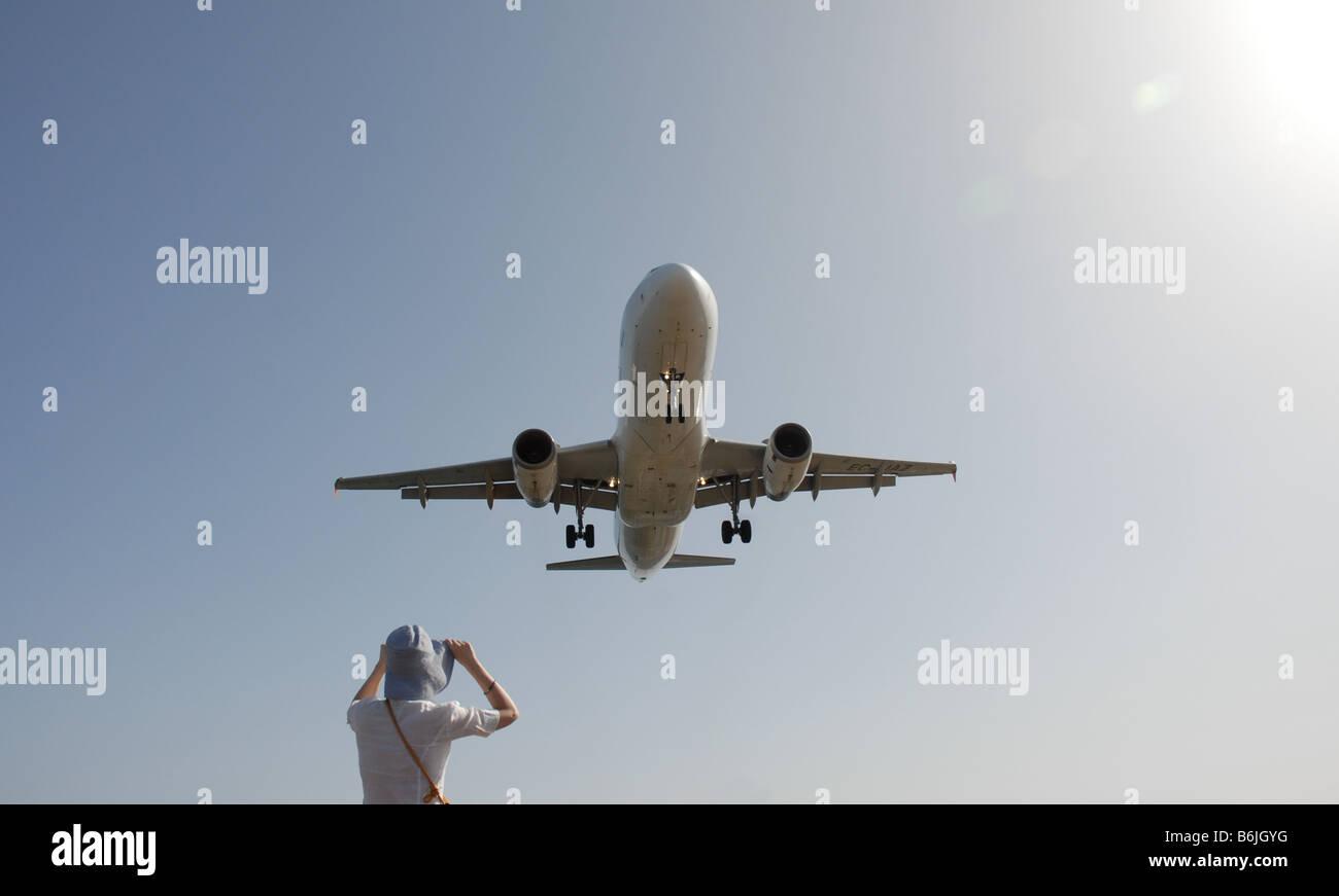 Eine Frau am Strand von Playa de Guasimeta Uhren ein Flugzeug kommt ins Land in Arrecife Flughafen Lanzarote auf Stockbild