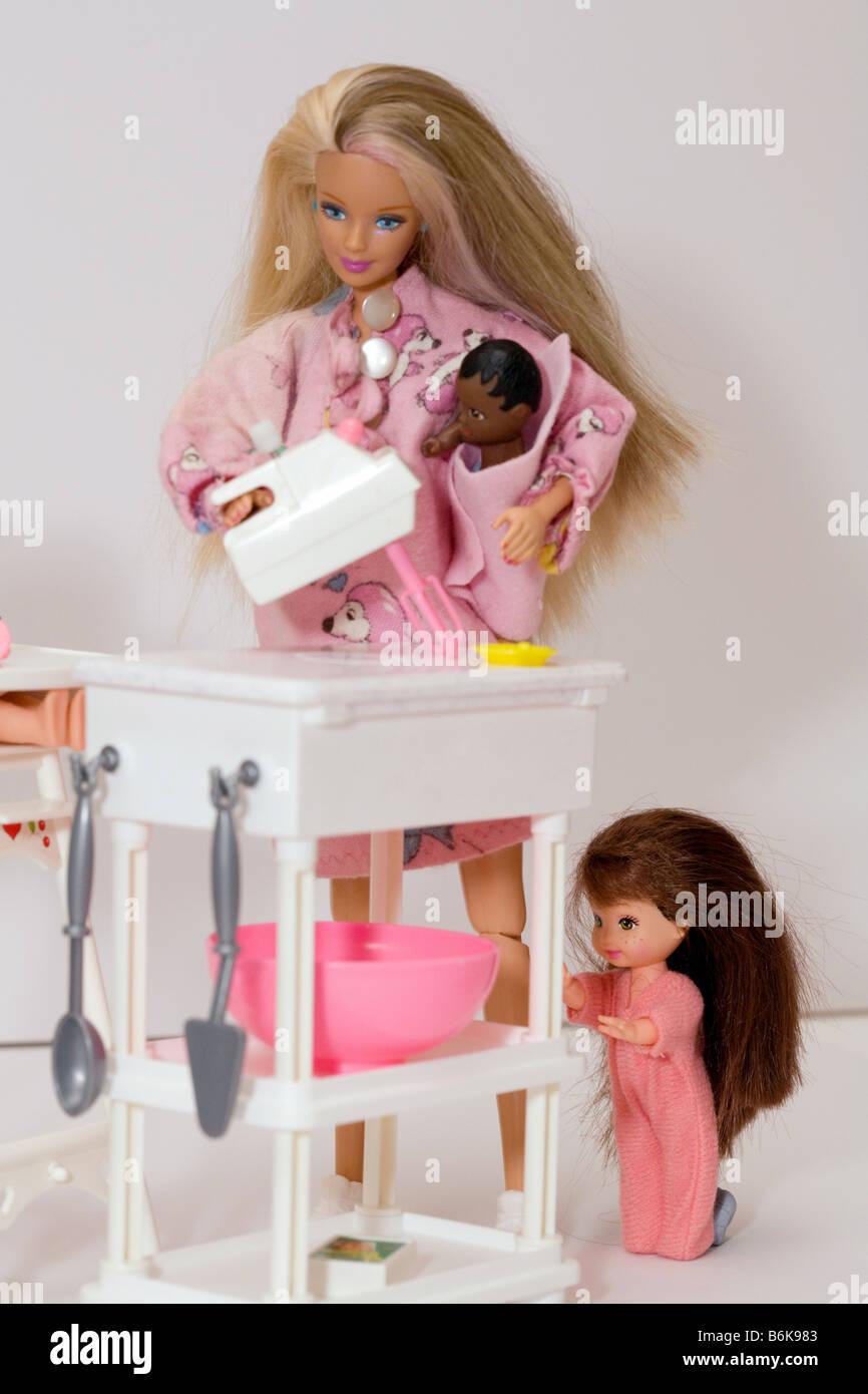 Mutter-Puppe arbeiten in ihrer Küche mit Kleinkind und Baby Iilustrating Konzept der alleinerziehenden Elternteil Stockbild