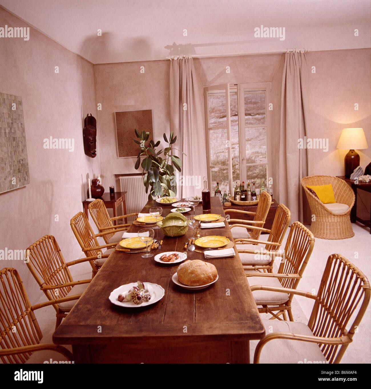 Rohrstuhlen An Lange Antike Tisch In Franzosischer Landhaus Esszimmer Mit Beige Gardinen An Franzosische Fenster Stockfotografie Alamy