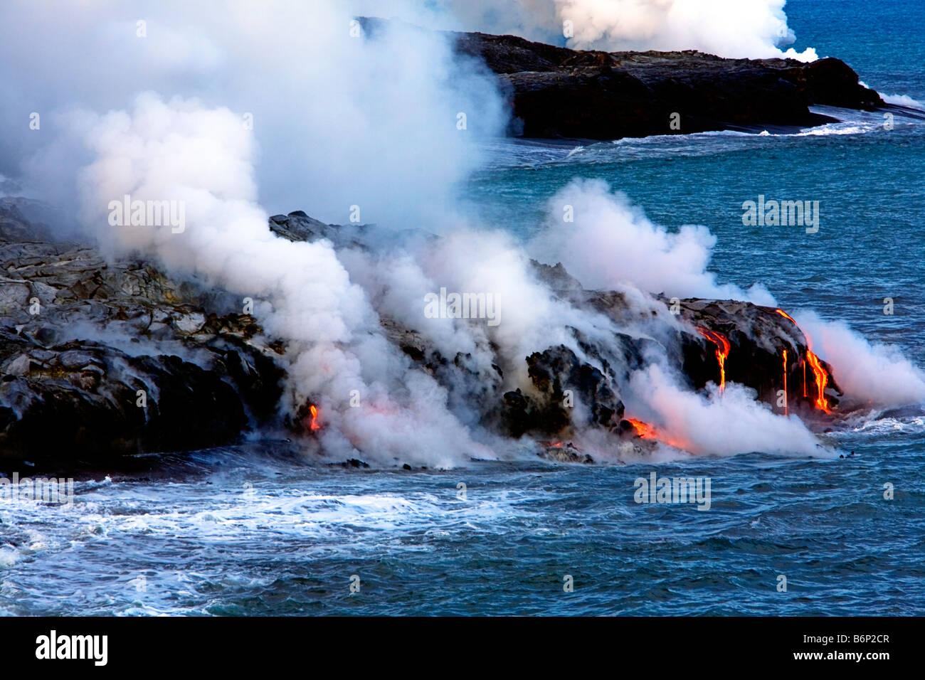 Bild der geschmolzene Lava fließt den Berg hinunter und ins Meer während Dampf steigt rund um Stockfoto