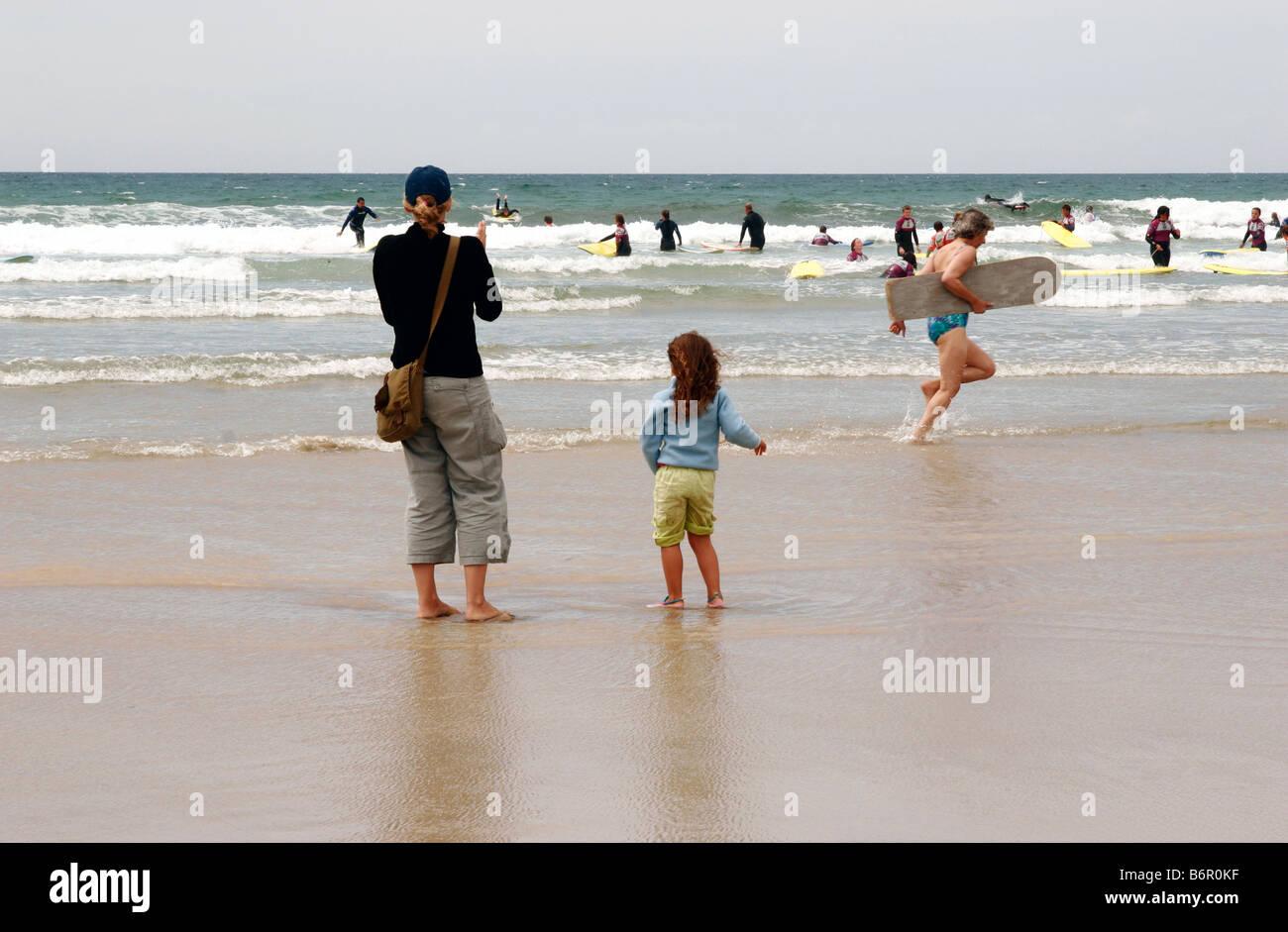 Mutter und Tochter gerade Menschen Surfen und Schwimmen am Polzeath sandigen Strand in Cornwall Stockfoto