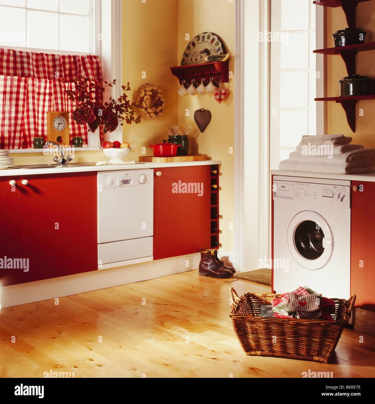 Korb Wäsche auf Holzboden vor Waschmaschine in der Küche mit roten ...