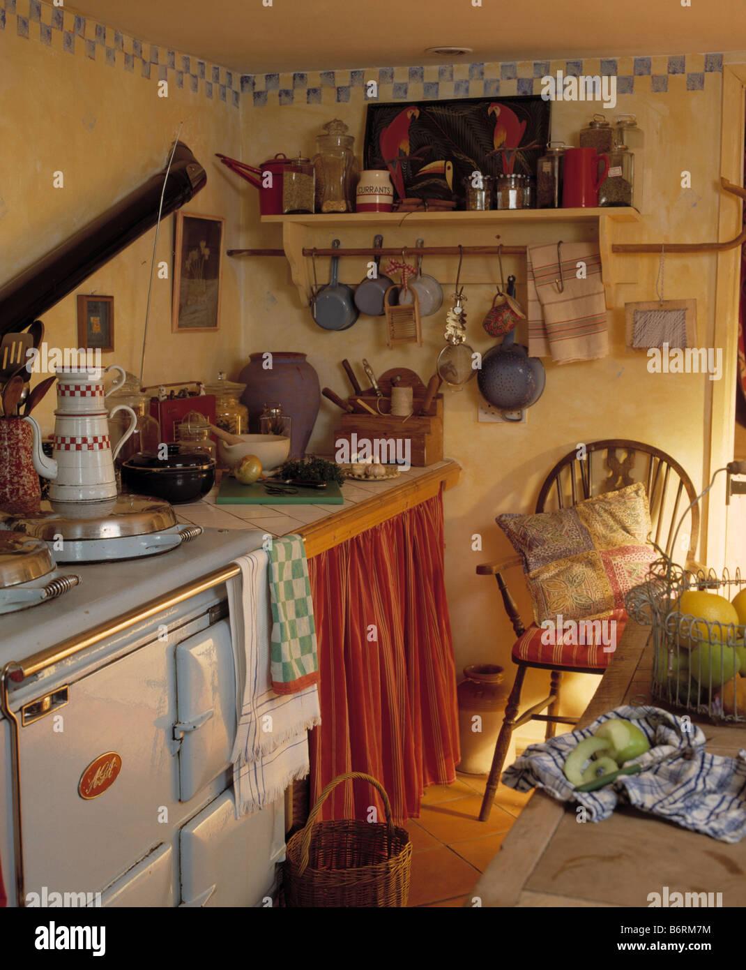 AGA-Ofen im Cottage-Küche mit Vorhang an Schrank und Hand