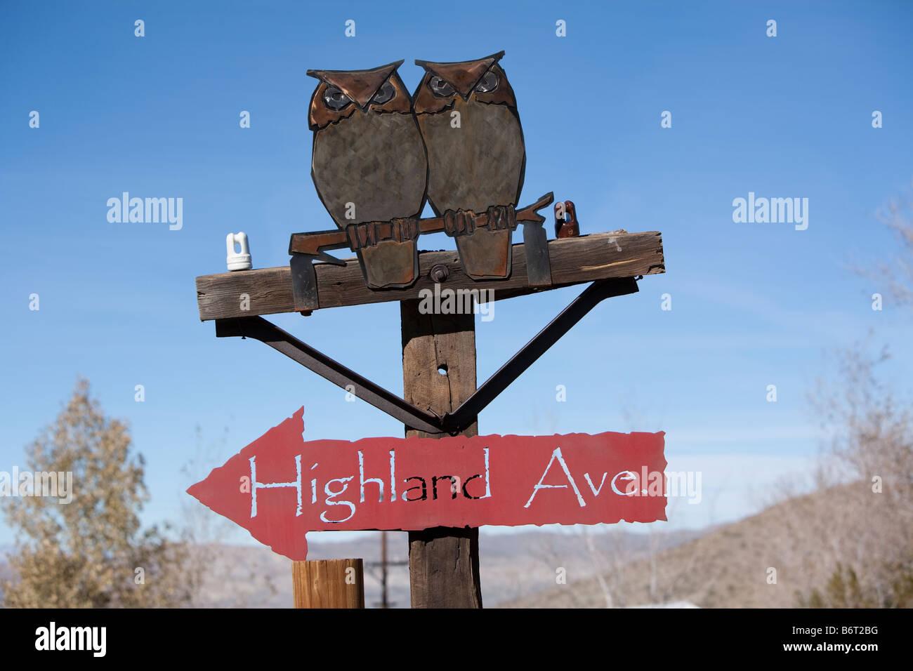 Dekoratives Schild mit zwei Metall-Eulen thront auf einem Schild mit Pfeil in die Richtung von Highland Ave. Stockbild
