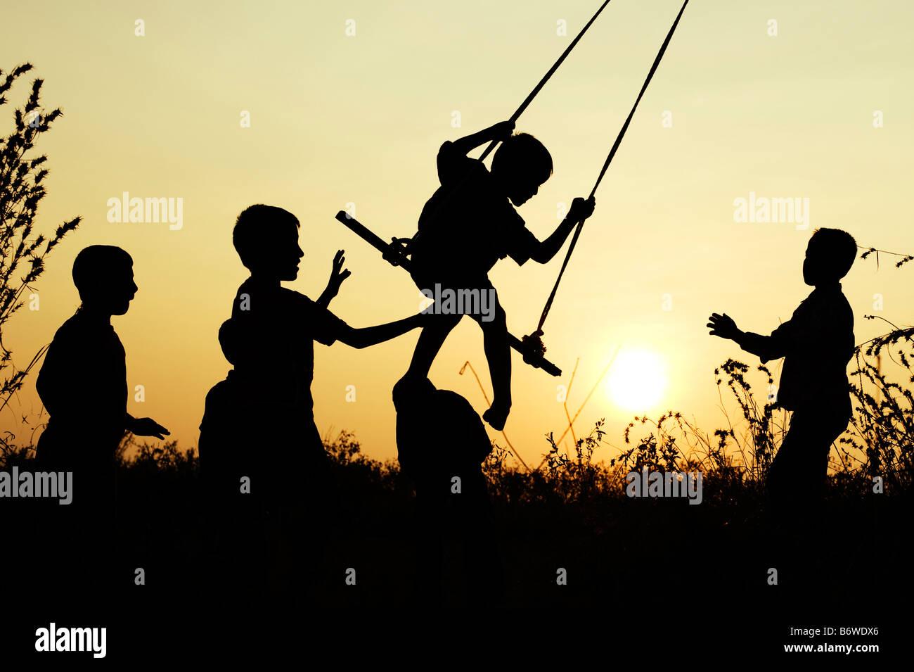 Silhouette der indischen Kinder spielen auf einem hausgemachten Schaukel in der Landschaft bei Sonnenuntergang. Stockfoto