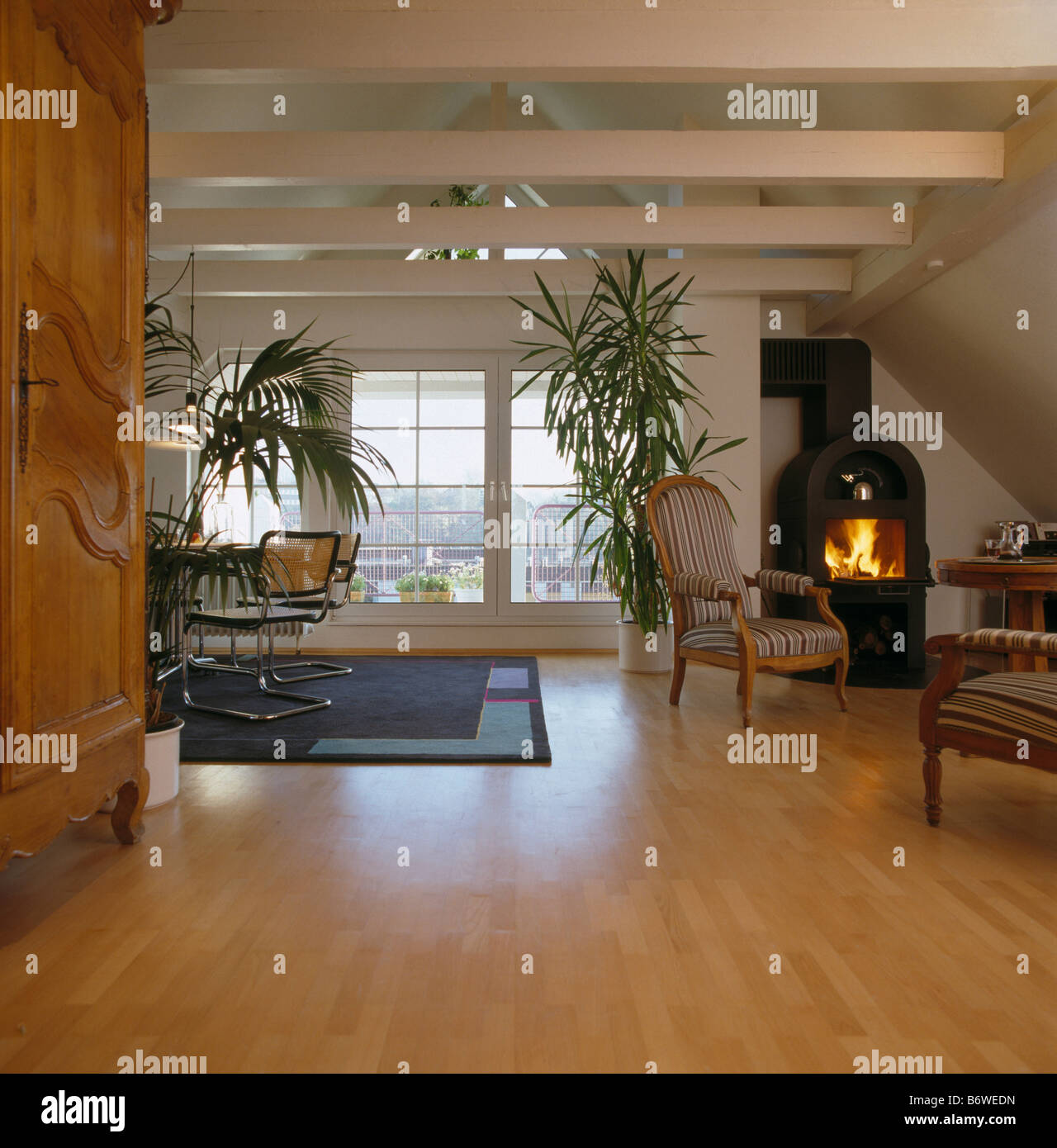 schwarzen gusseisen ofen mit angez ndeten feuer in moderne offene wohnzimmer mit hohen. Black Bedroom Furniture Sets. Home Design Ideas