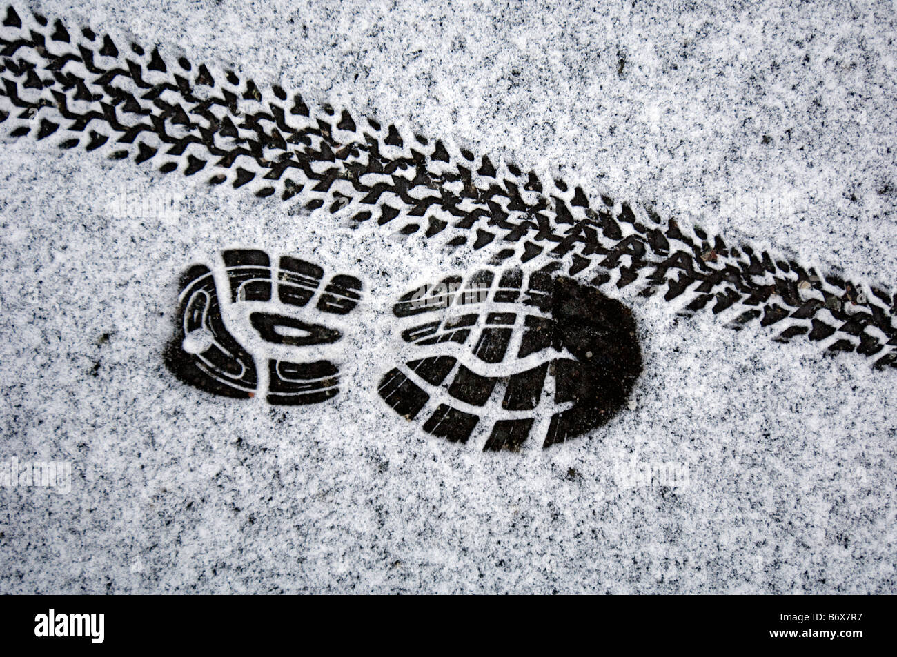 Kaltes Wetter Training A Jogger Trainingsschuh print und ein Mountainbike Reifen Strecke auf einer Prise Pulverschnee Stockbild