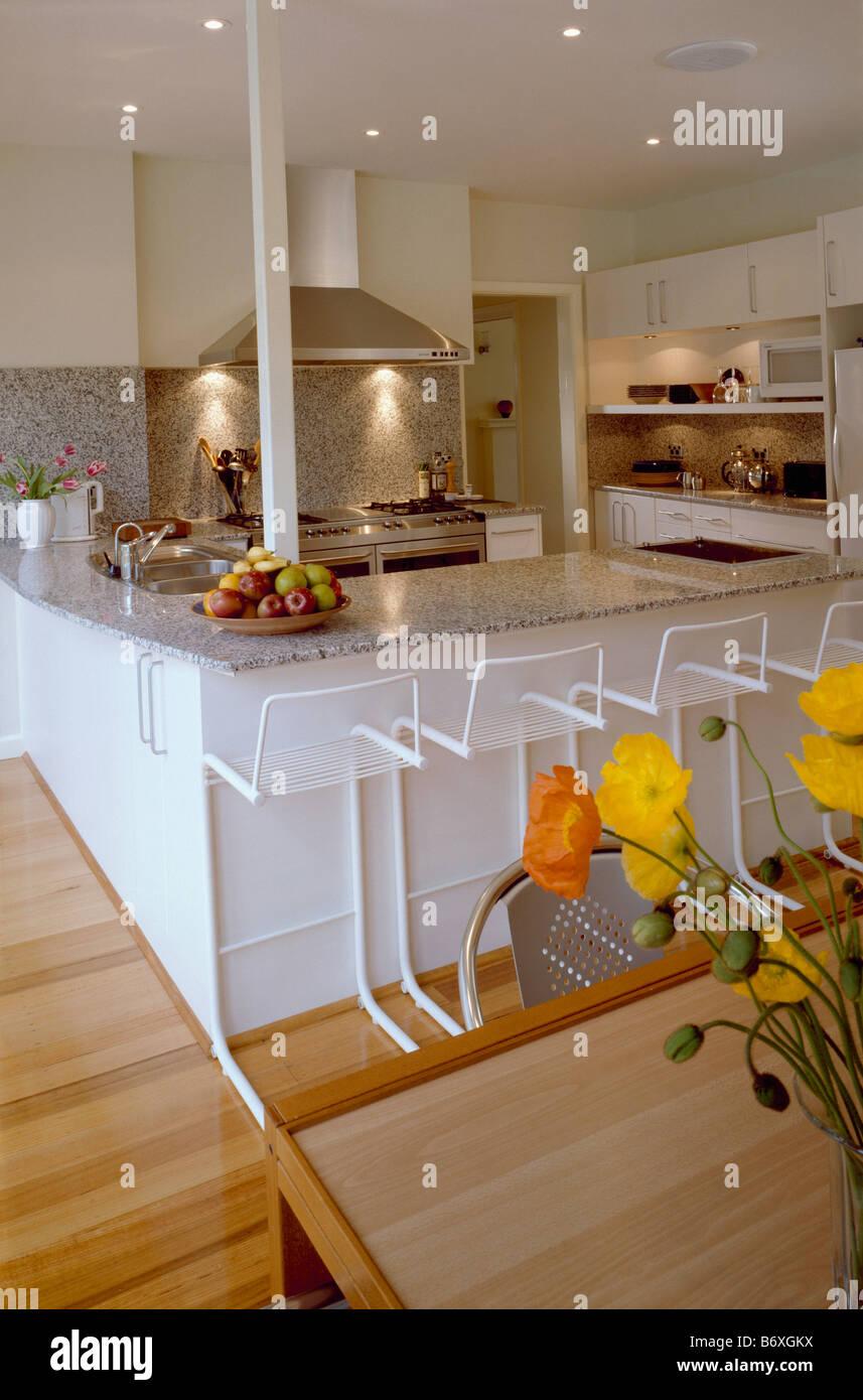 Weißer Hocker an Frühstücksbar in große, moderne weiße Küche mit ...