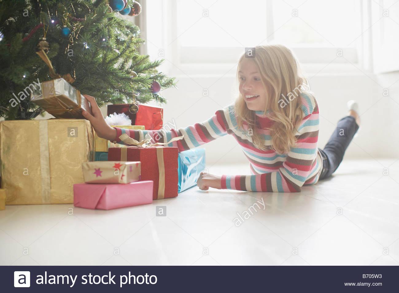 Mädchen auf der Suche auf Weihnachtsgeschenke unter Baum Stockfoto ...