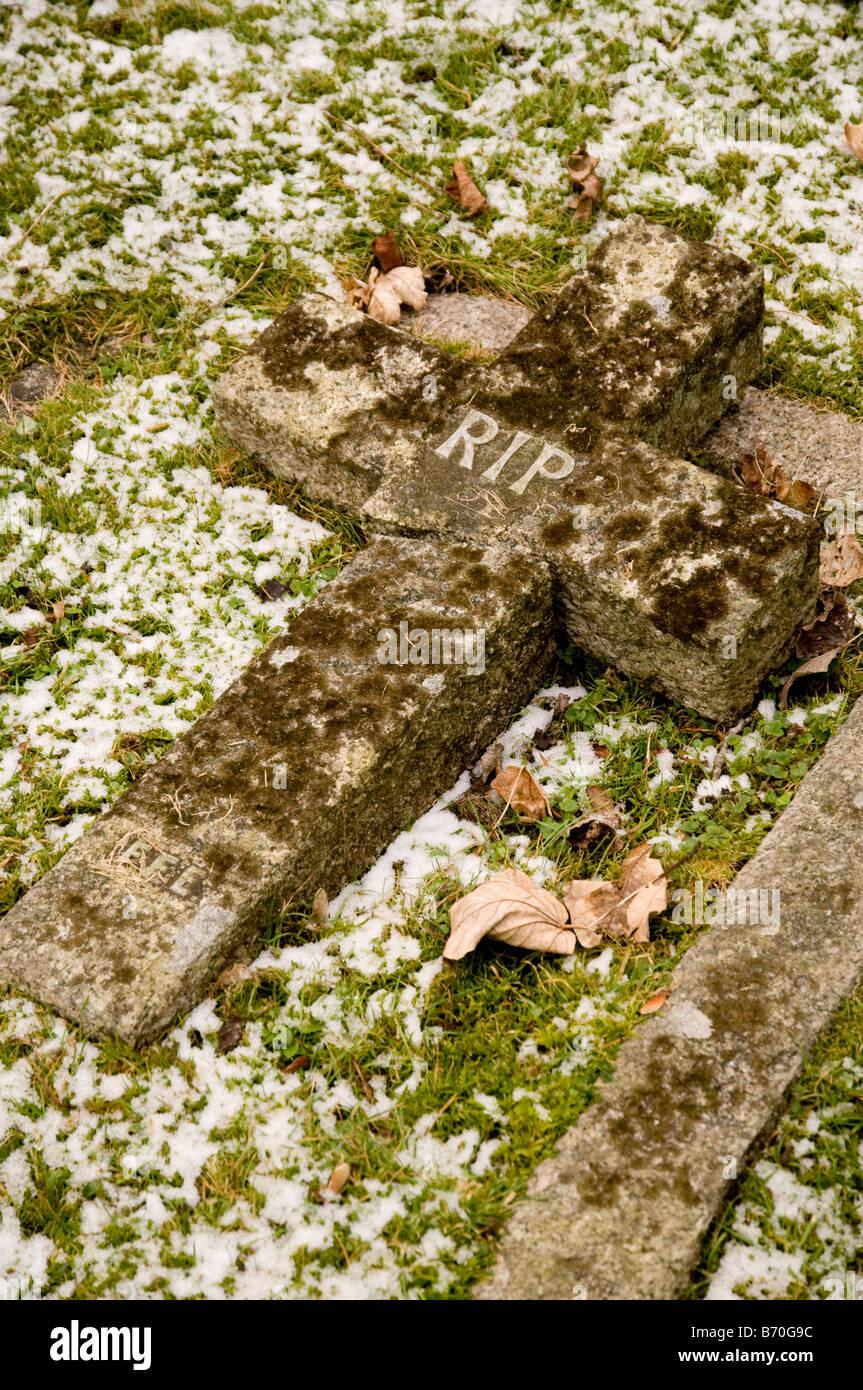 """Eine kreuzförmige Grabstein mit den Initialen """"RIP"""", liegend auf dem Boden gebrochen. Stockbild"""