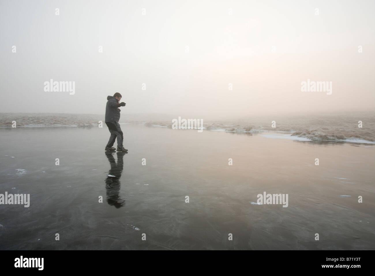 Ein Wanderer auf einen gefrorenen Tarn nahe dem Gipfel des Caudale Moor in den Lake District-UK Stockbild