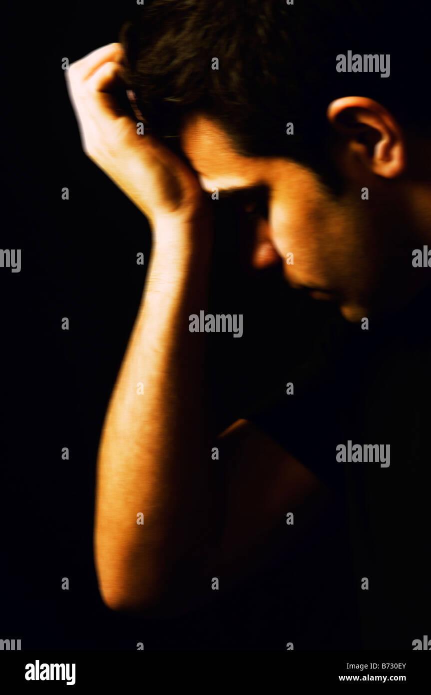 Junger Mann Kopf in die hand gedrückt Stockfoto