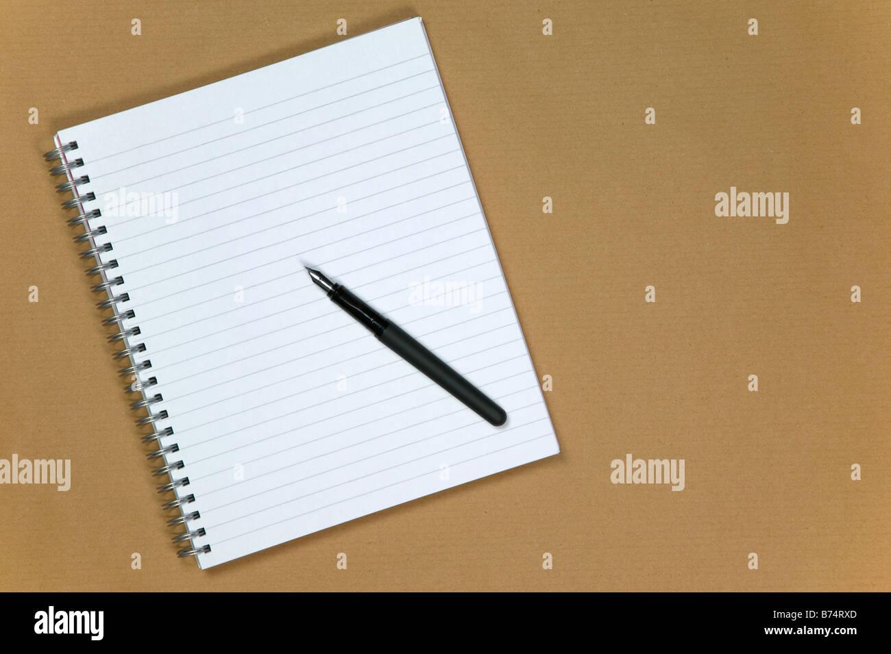 Spiral-Notizbuch und Füllfederhalter auf braunem Papierhintergrund Stockfoto