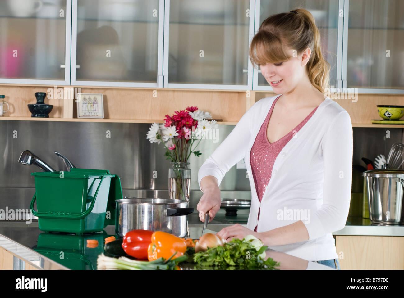 Frau Schneiden von Gemüse, mit grünen Küche Kompost-Eimer zum ...