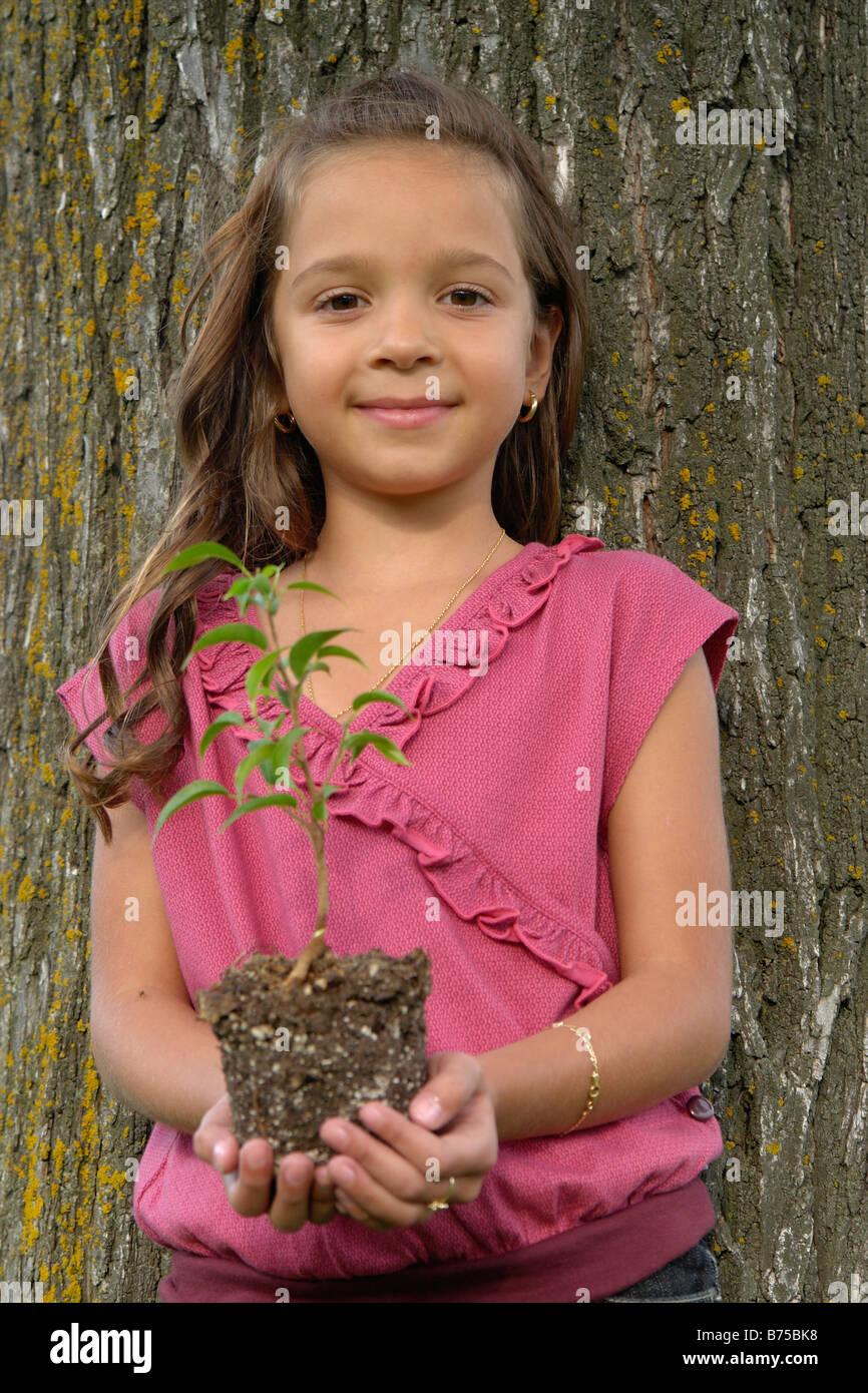 Sieben Jahre altes Mädchen hält Sämling neben Baum, Winnipeg, Kanada ...