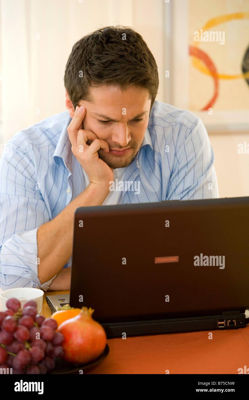 Mann Arbeitet Zu Hause Mit Einem Notebook, Mann arbeitet zu Hause auf notebook Stockbild