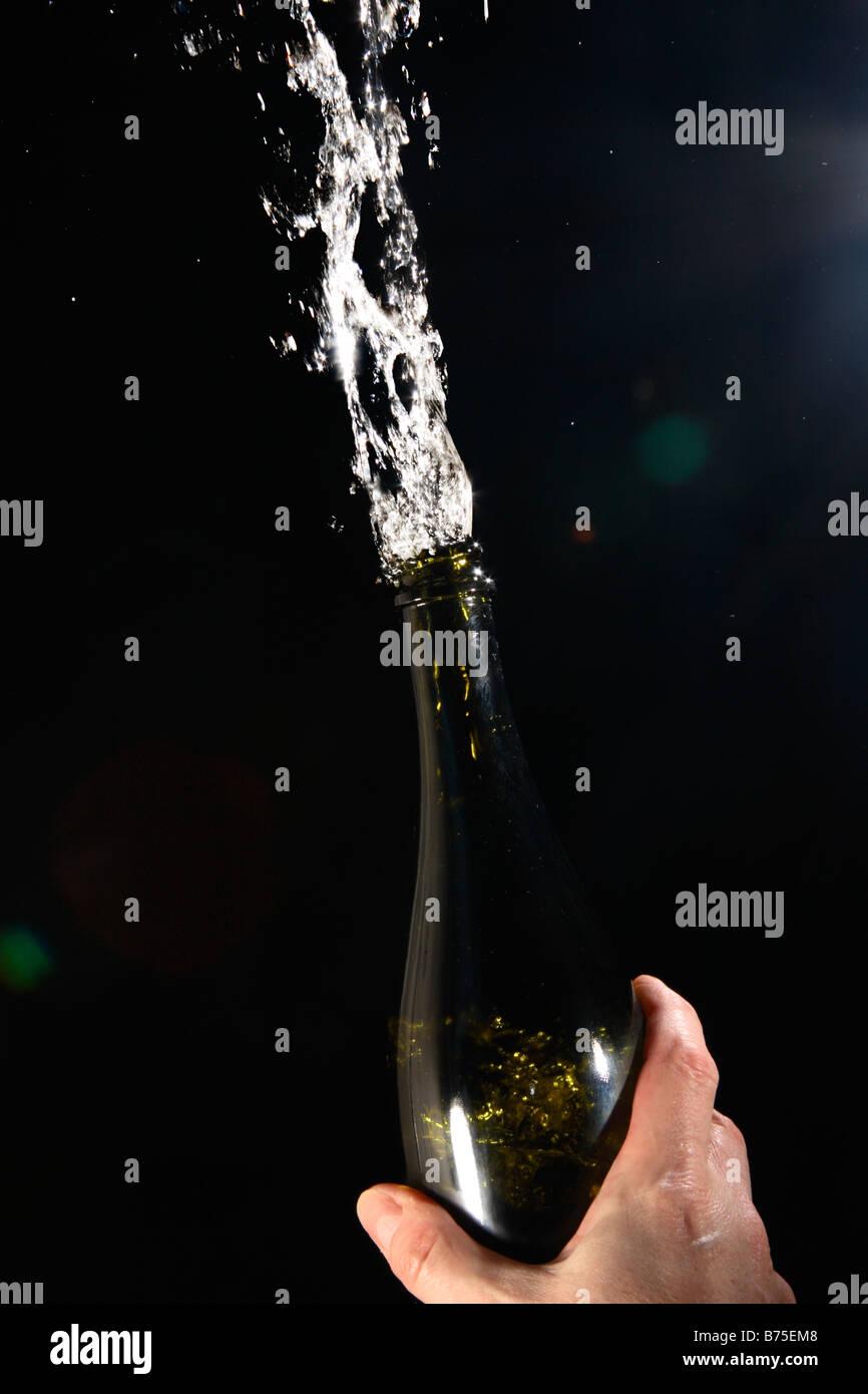 Champagner aus einer Flasche auf schwarzem Hintergrund. Stockbild
