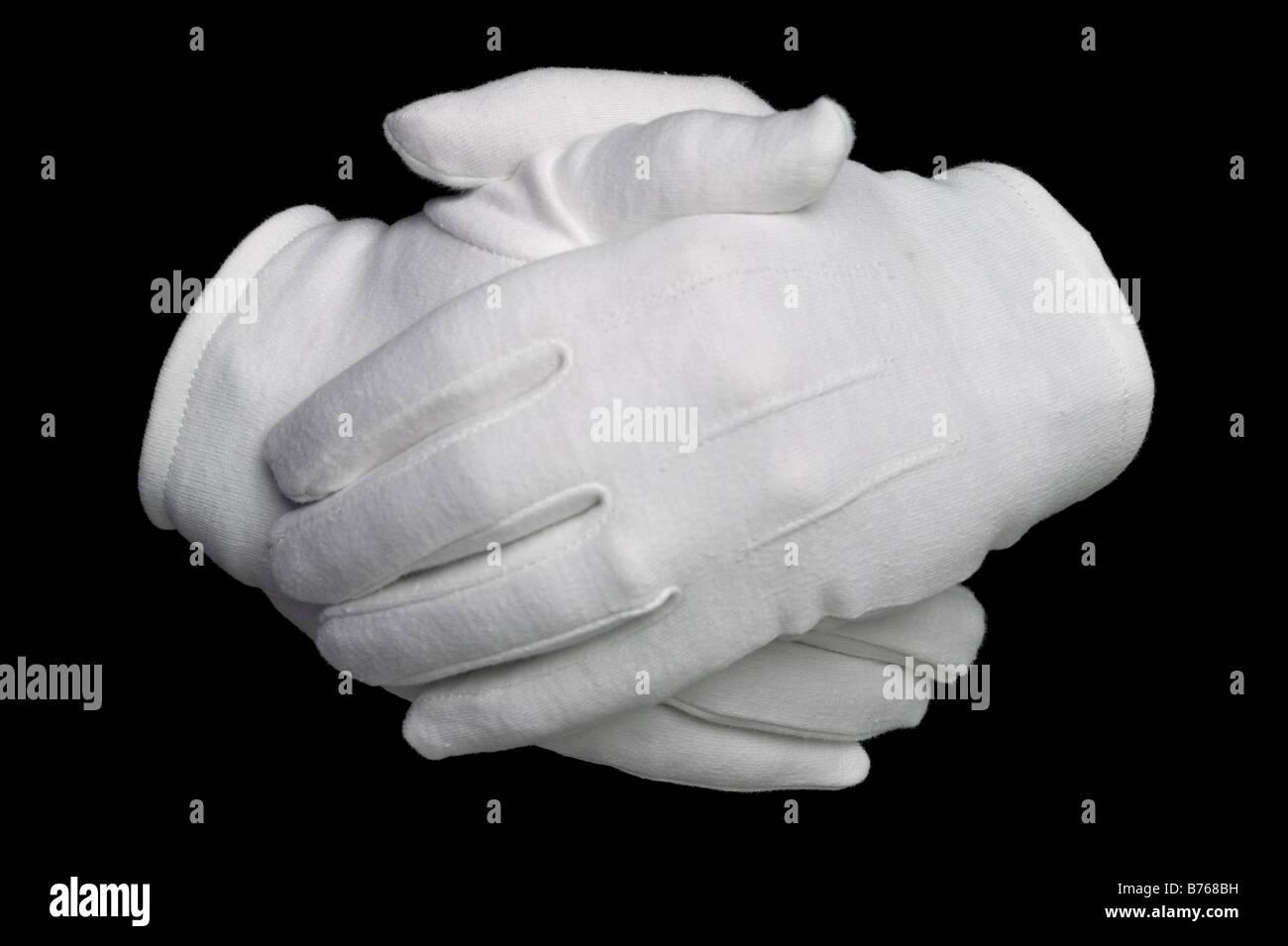 Hände in weiße Baumwollhandschuhe auf schwarzem Hintergrund isoliert Stockbild