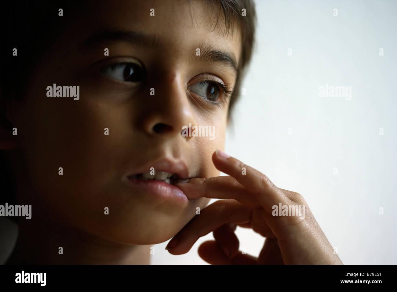 Sechs Jahre alter Junge kaut Nägel Stockbild