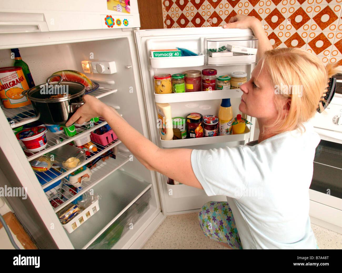 Kühlschrank Krug : Frau lebensmittel in den kühlschrank in der küche stockfoto bild