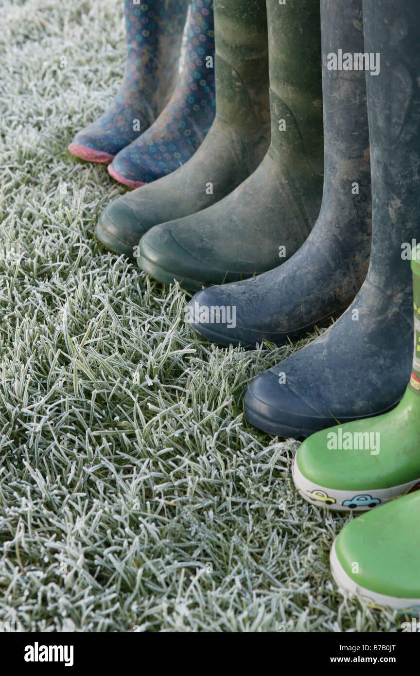 eine Aufstellung einer Familie von Wellington Stiefel links auf einige frostigen grünen Rasen bietet ein Konzeptbild Stockfoto