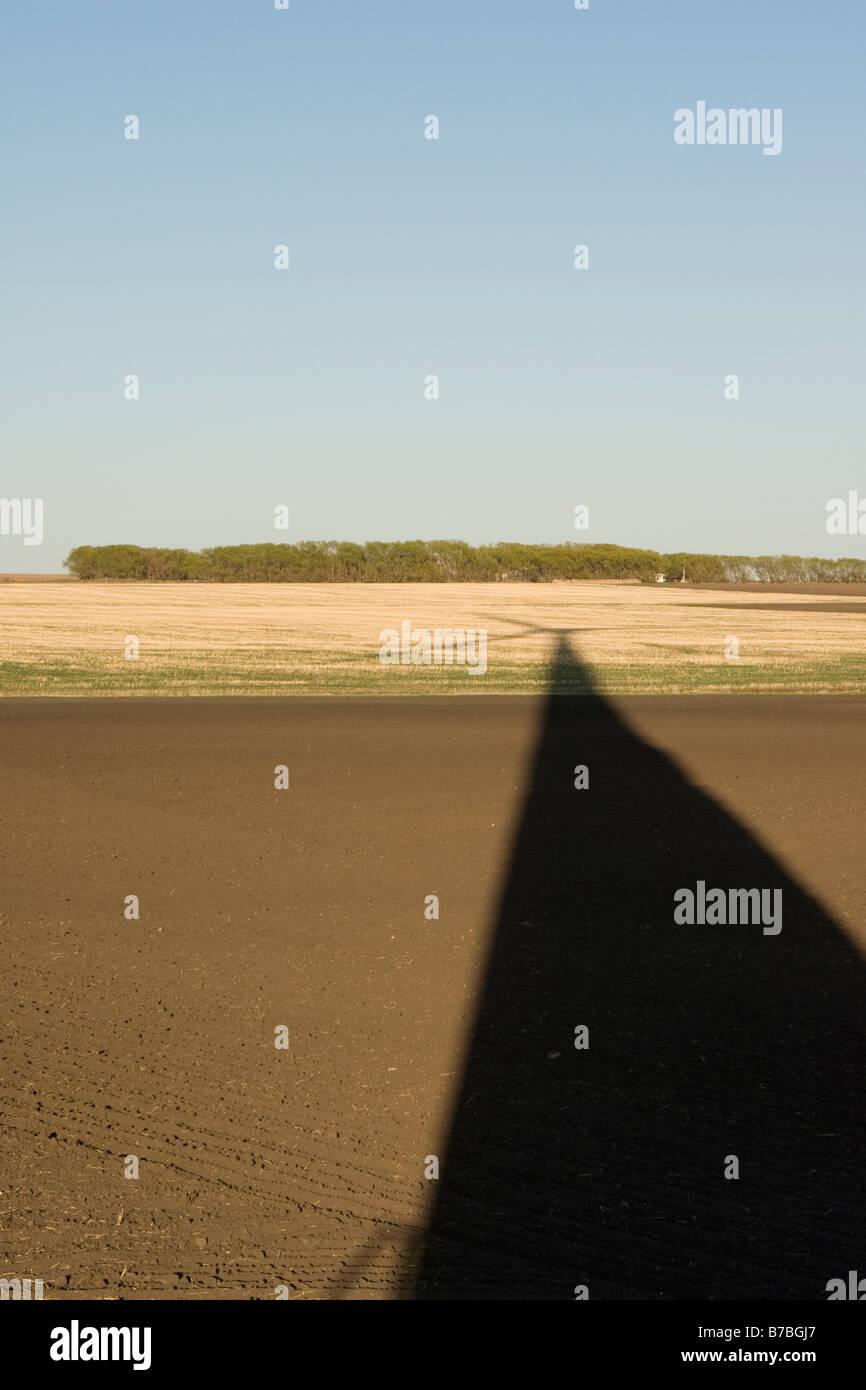 Lange Schatten der Windkraftanlage auf Boden Stockbild