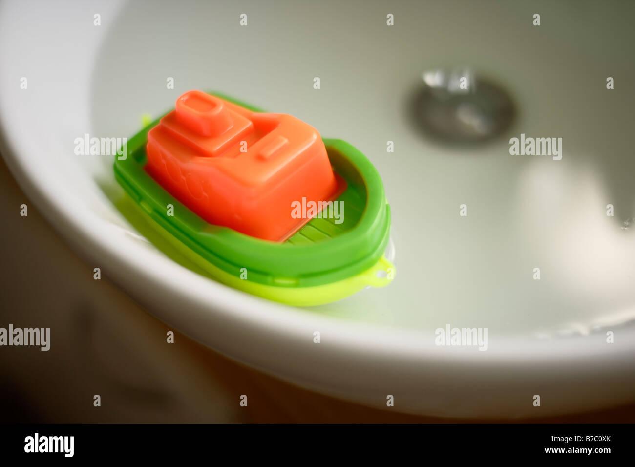 Des Kindes Kunststoff Spielzeugboot in Spüle voll Wasser Stockbild