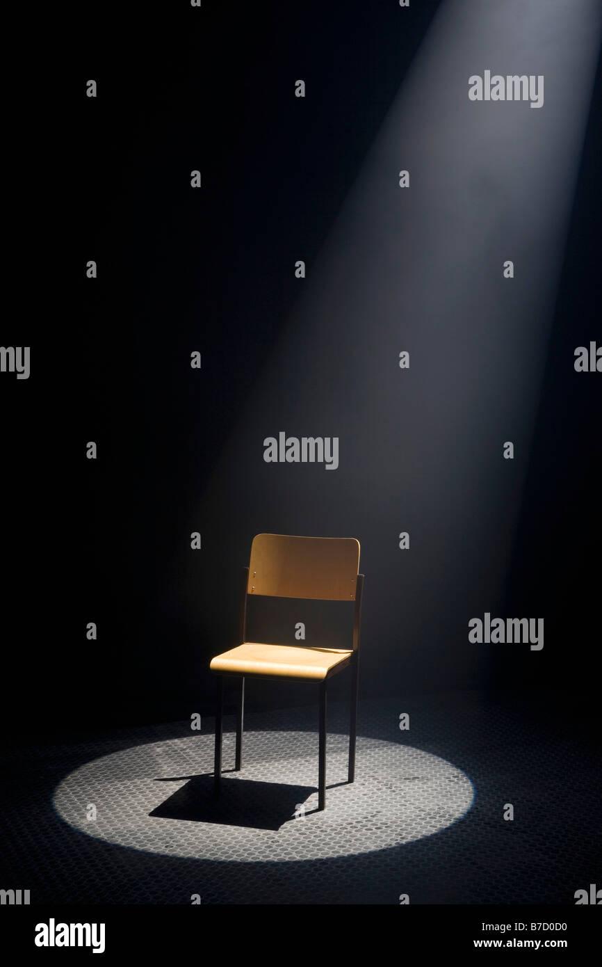 Ein Spot beleuchtet leeren Stuhl Stockbild