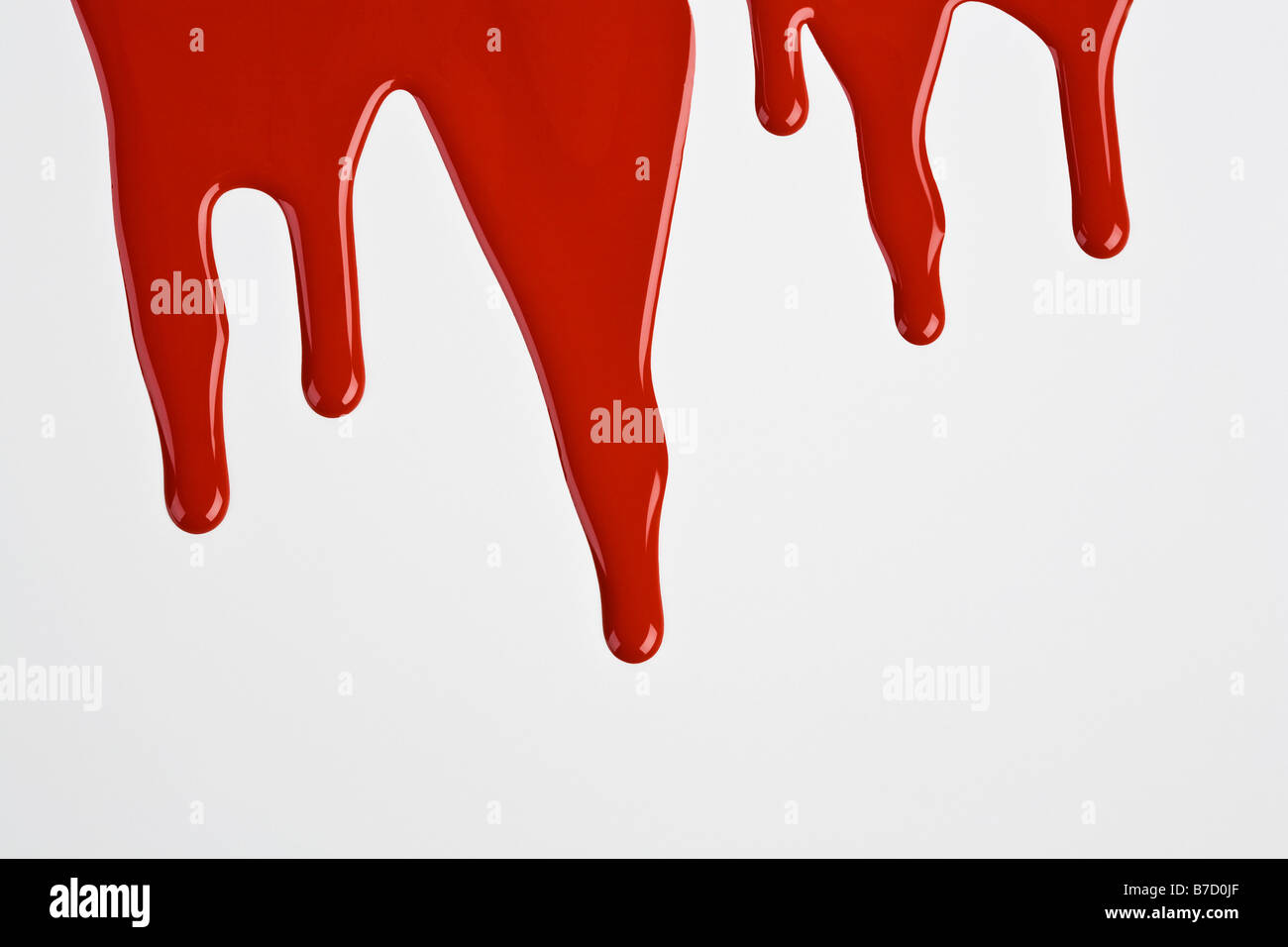 Rote Farbe tropfte eine weiße Wand Stockfoto