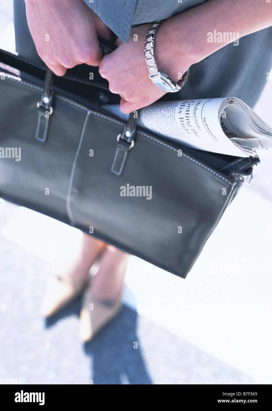 Frau Holding Tasche mit Zeitung Stockfoto