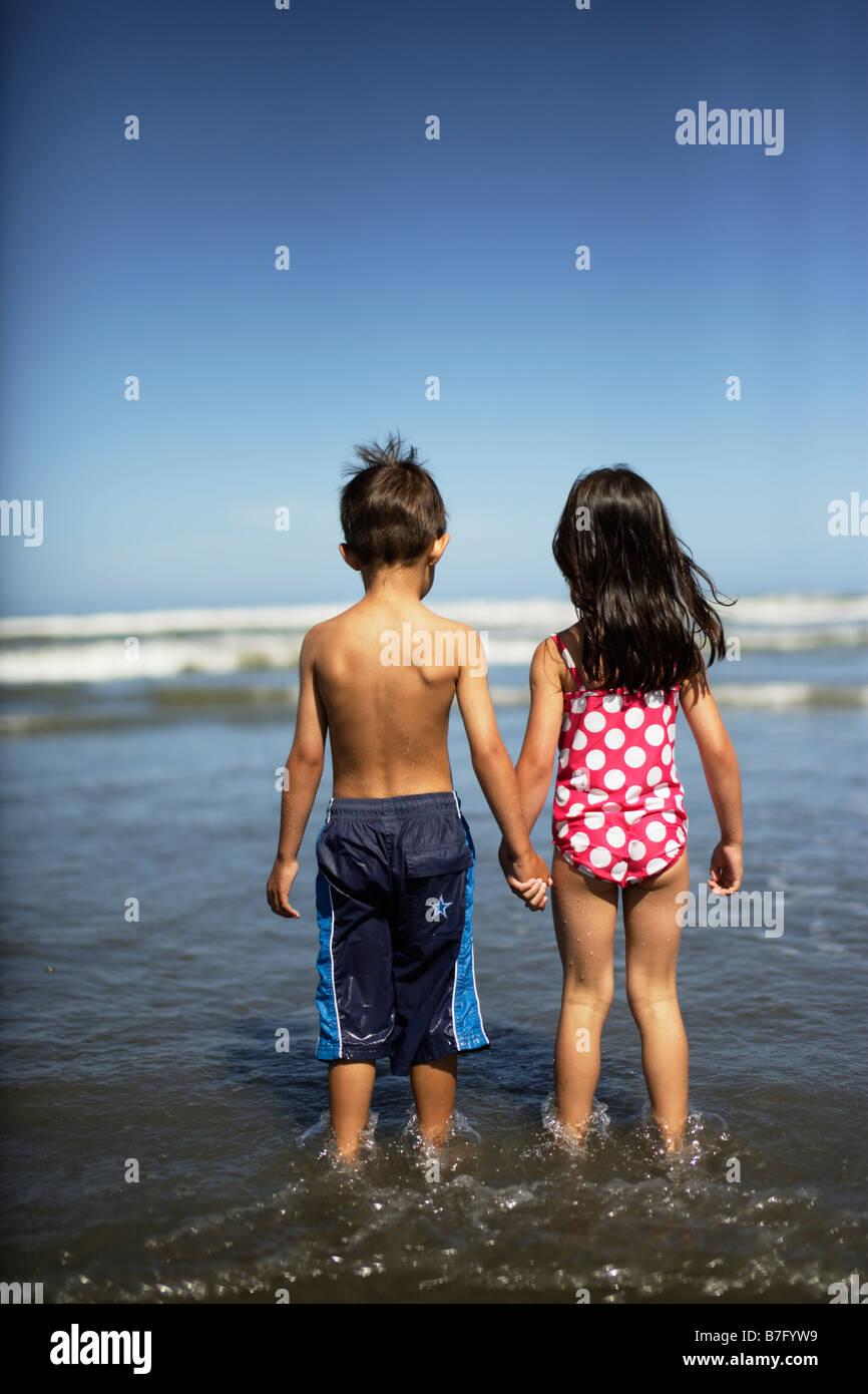 Himatangi Beach Neuseeland. Mädchen im Alter von fünf und jungen im Alter von sechs Blick heraus zum Meer. Stockbild