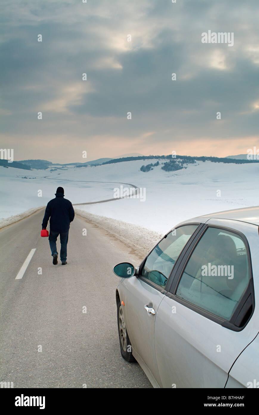 Mann beginnt den langen Weg auf einer abgelegenen Landstraße im Winter Kraftstoff für sein Auto kaputt Stockbild