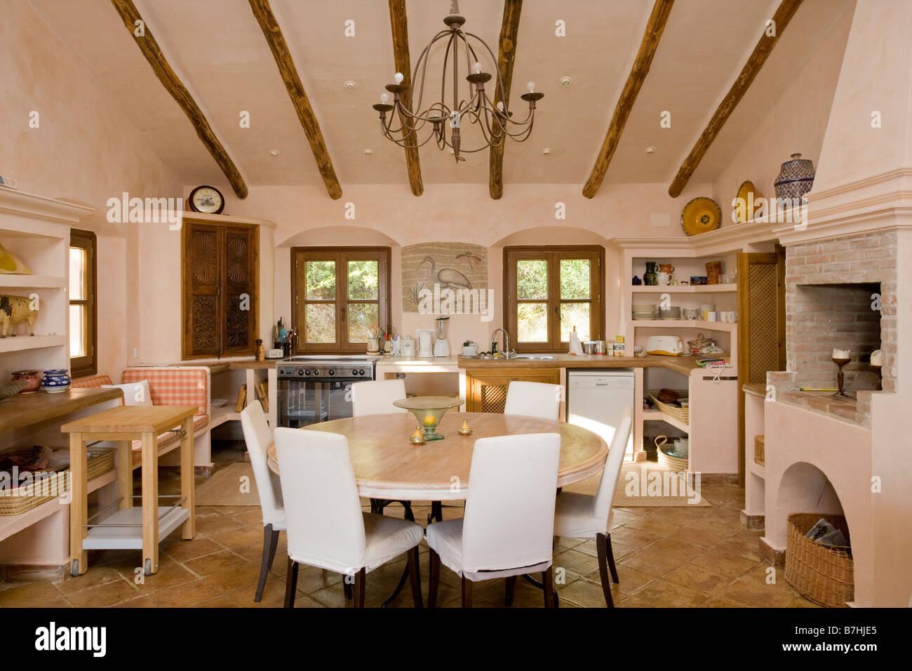 Weiße Loosecovers auf Stühlen am runden Tisch im rustikalen ...