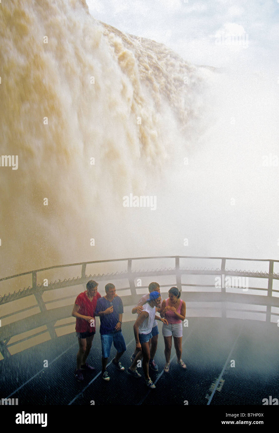 Brasilien-Seite der Iguazu Wasserfälle mit Touristen in Spray auf Aussichtsplattform Stockbild