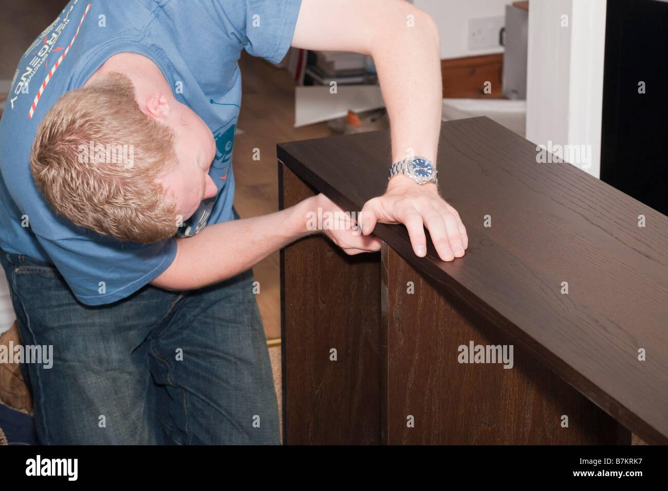 Tausendjährige junger Mann Montage einen Flachbild-pack Holzregal zu Hause. England Großbritannien Großbritannien Stockbild