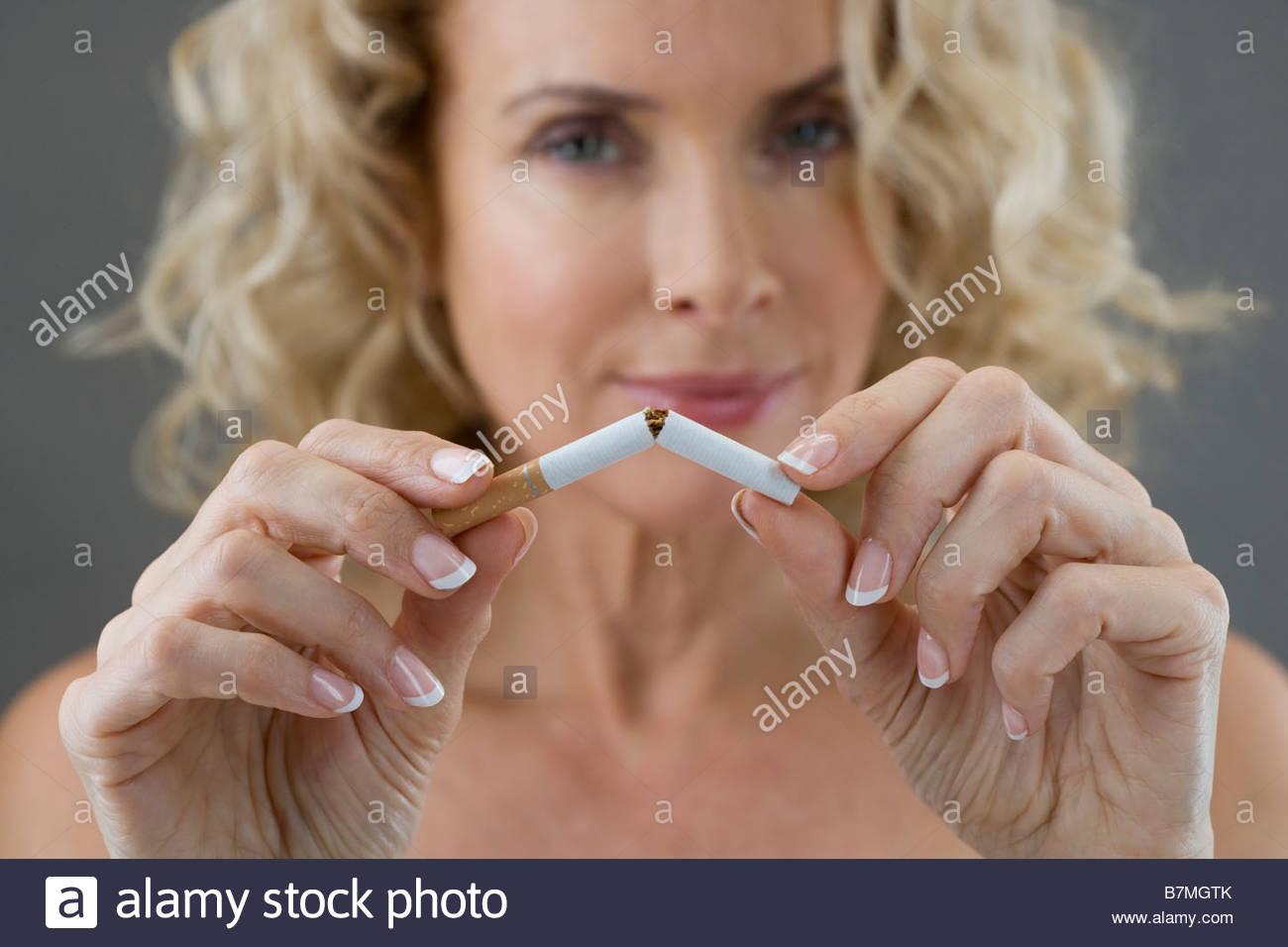 Eine Frau mittleren Alters, eine Zigarette in zwei Hälften brechen Stockbild