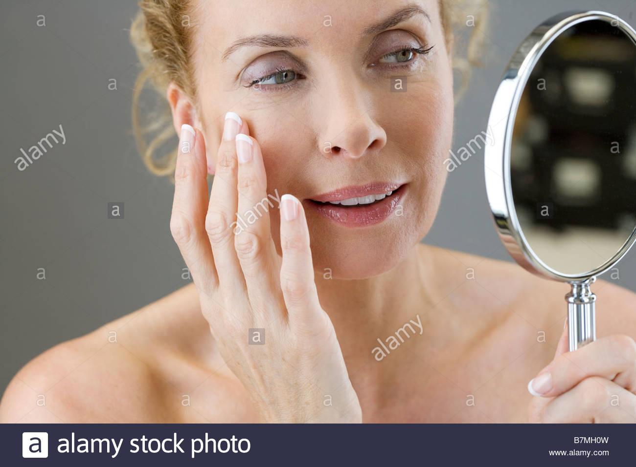 Eine Frau mittleren Alters, die ihr Gesicht im Spiegel zu betrachten Stockbild