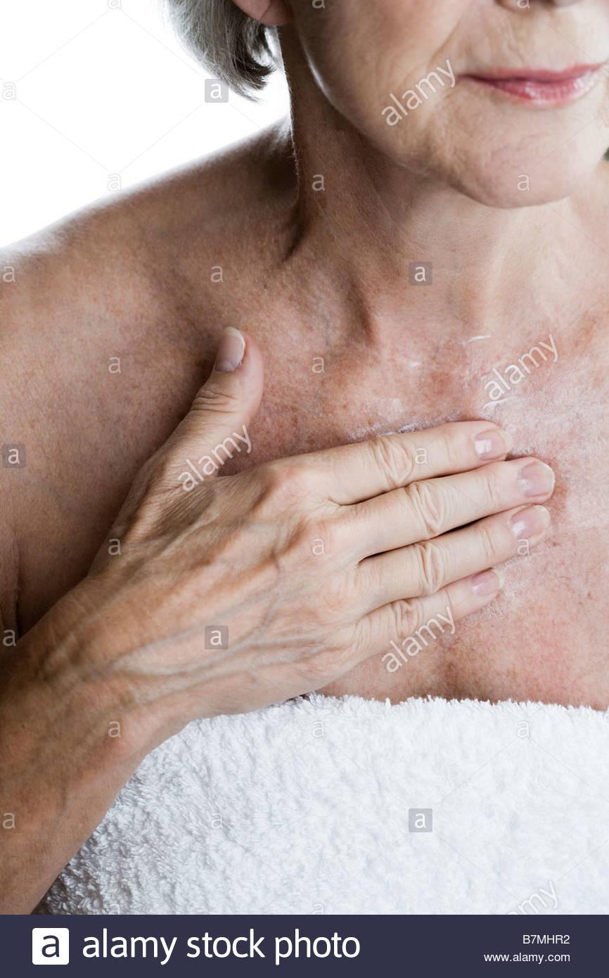 Eine ältere Frau anwenden Feuchtigkeitscreme auf ihrer Brust Stockfoto