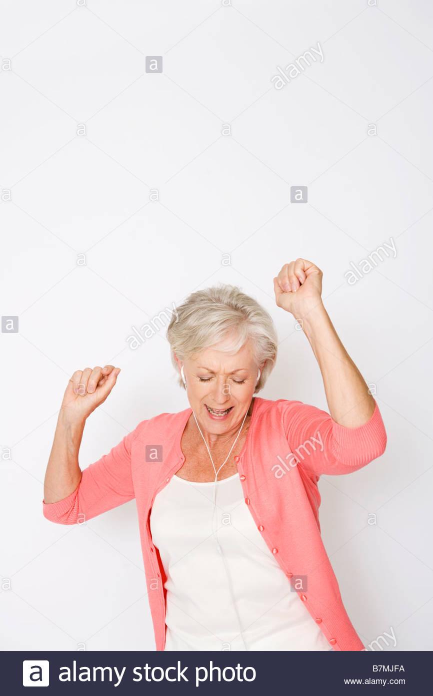 Eine ältere Frau tanzen zu Musik auf einen MP3-player Stockbild