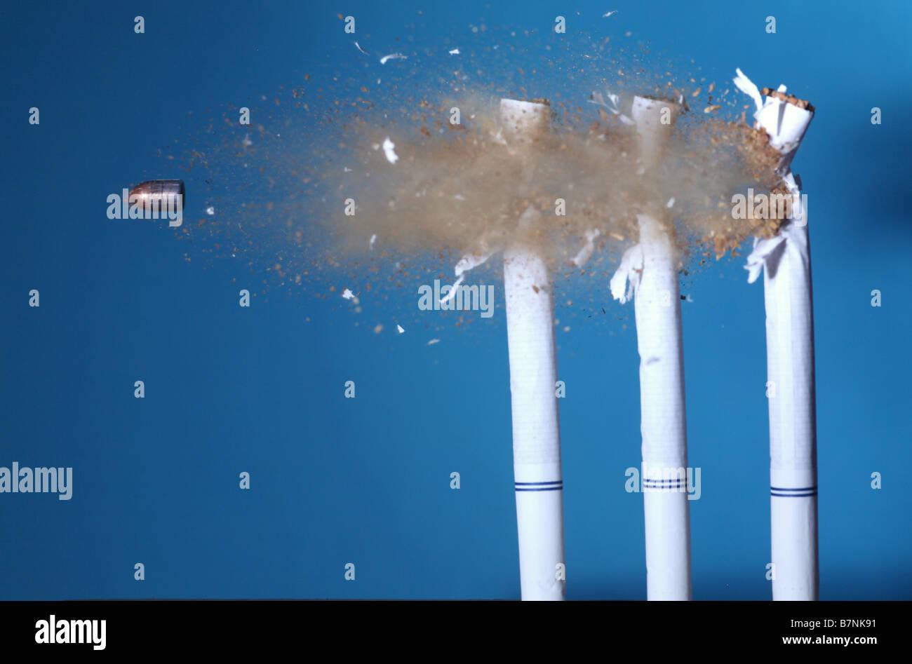 Eine Kugel trifft Zigaretten Stockbild