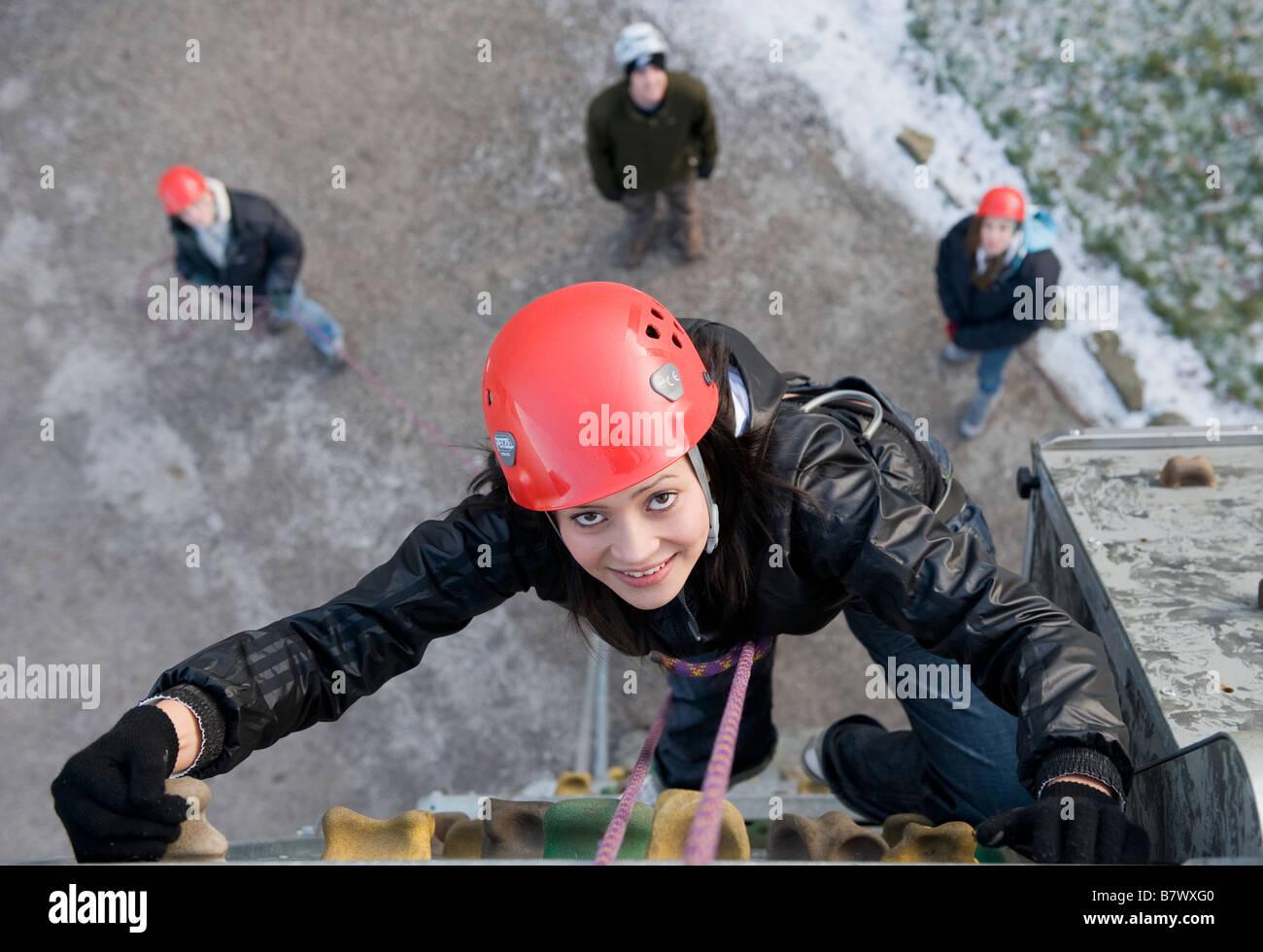 Junge Frau auf einer Kletterwand mit Freunden unten. Stockbild