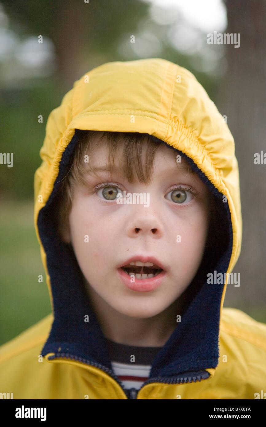 sechs Jahre alter Junge trägt einen gelben Regenmantel Kamera mit großen Augen starrte Stockbild