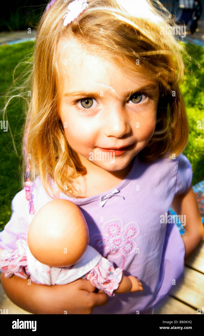 kleines Mädchen hält Babydoll glücklich Stockfoto
