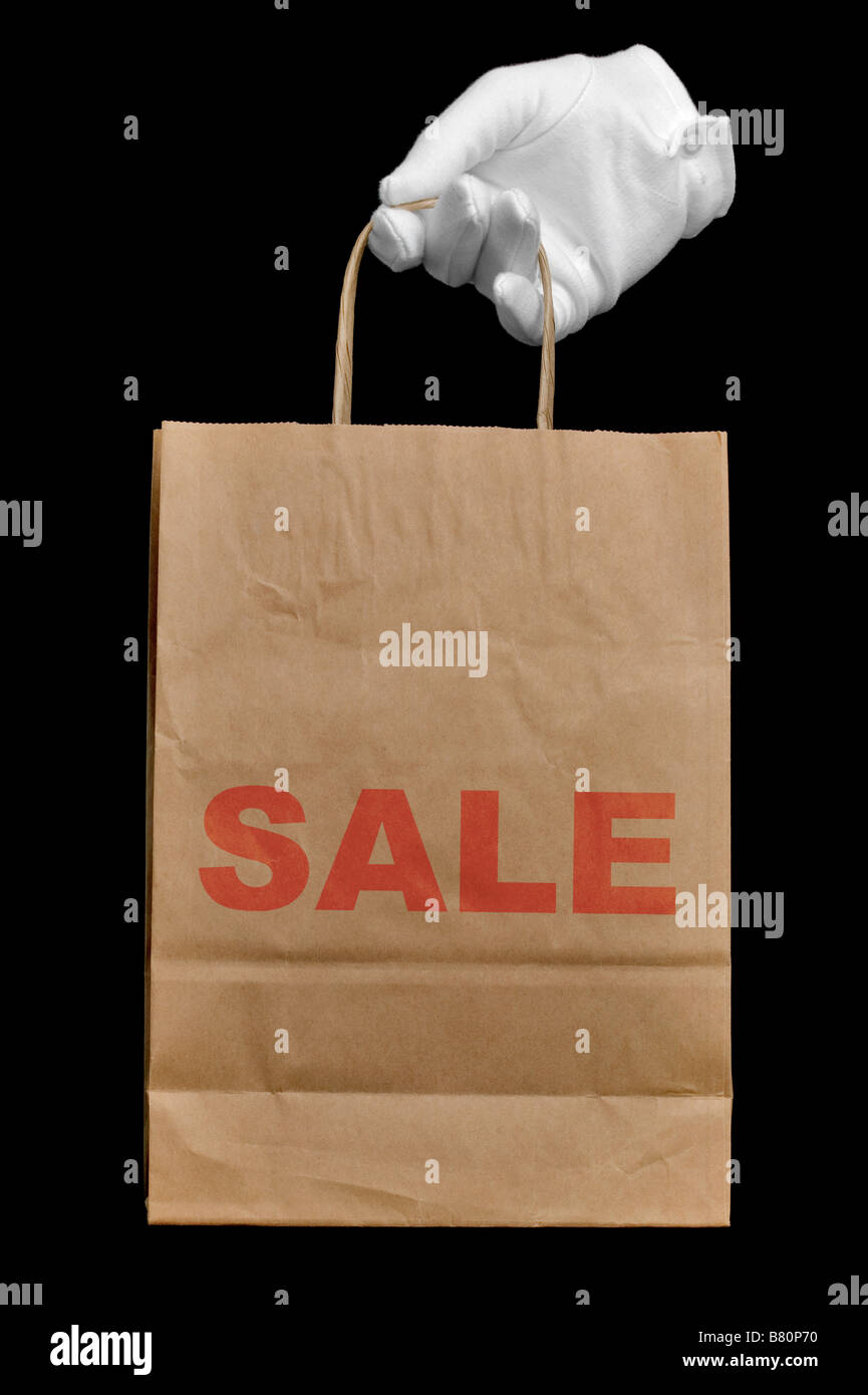 Geben Sie einen weißen Handschuh hält eine braune Recyclingpapier-Einkaufstasche mit dem Wort Verkauf Stockbild
