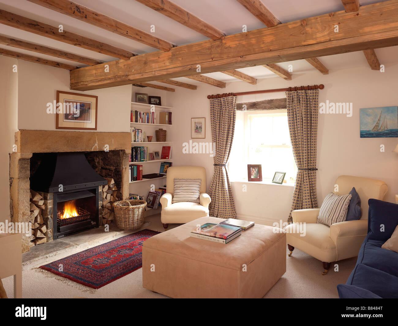 land stil wohnzimmer mit brennenden kaminfeuer und creme m bel mit karierte vorh nge und. Black Bedroom Furniture Sets. Home Design Ideas